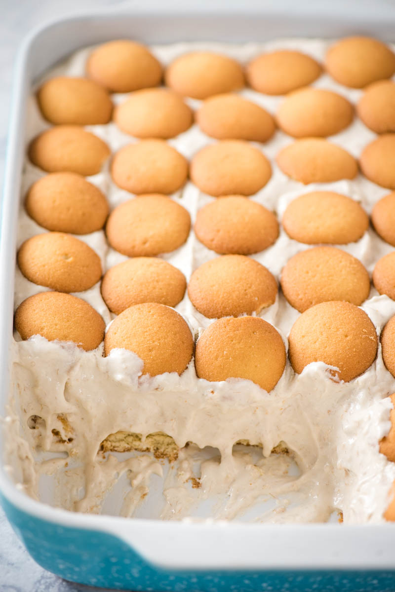 easy banana pudding layered with vanilla wafers in blue baking dish