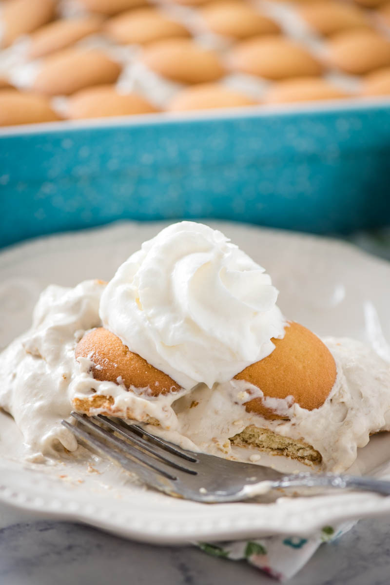 best banana pudding with vanilla wafers and whipped topping on white plate with fork