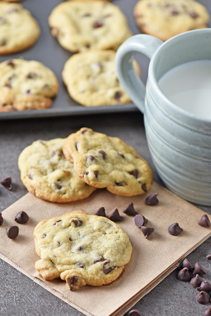 chewy chocolate chip cookies and milk on gray countertop