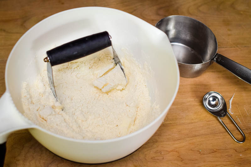 dry ingredients for making shortcake biscuits for strawberry shortcake recipe in white mixing bowl with pastry blender