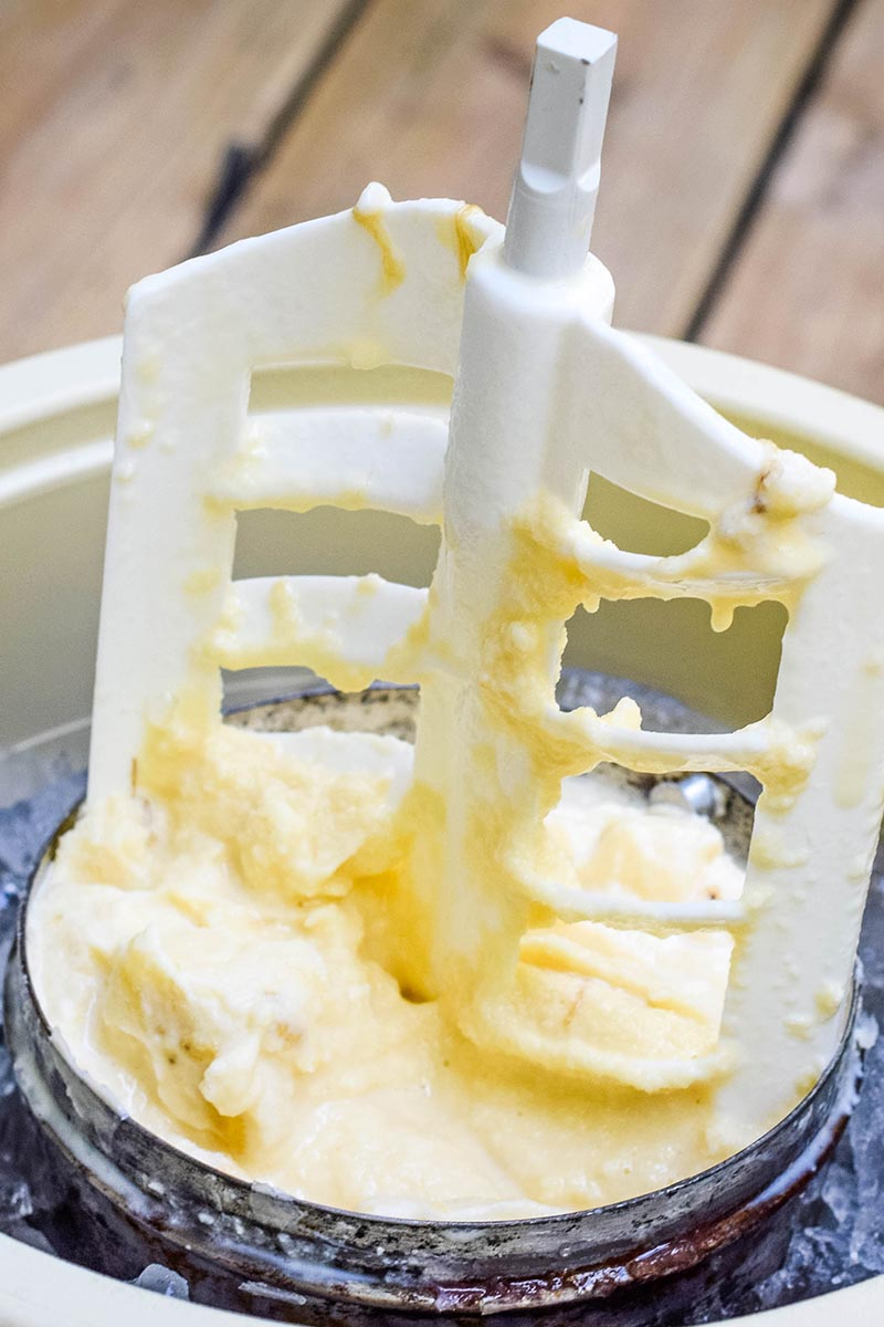 removing churning paddle from homemade banana ice cream in ice cream maker