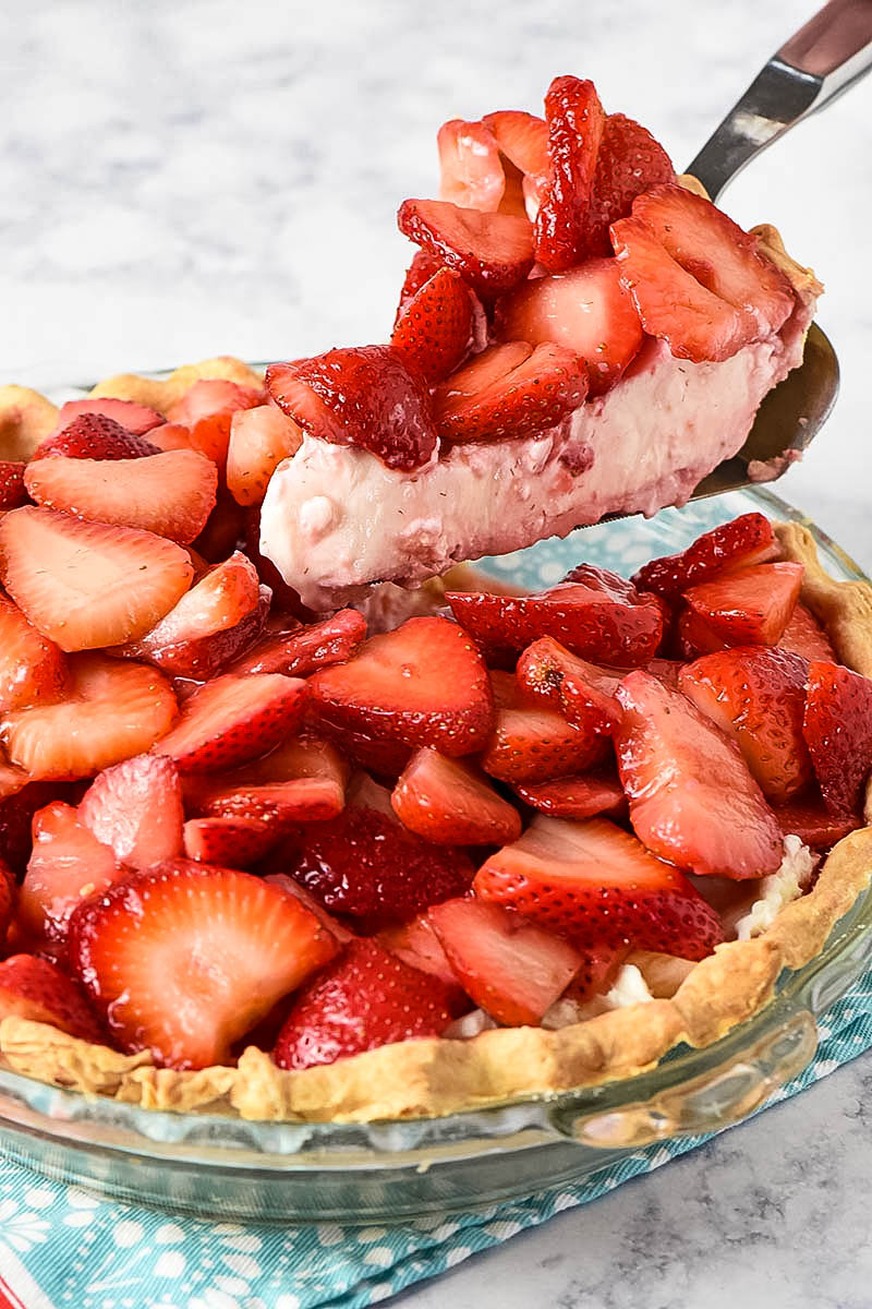slicing no bake strawberry cream pie with pie server
