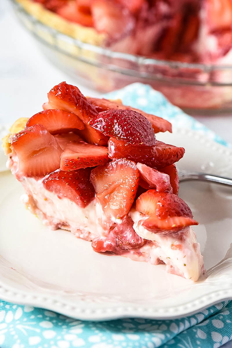 slice of strawberry pie on white plate with fork