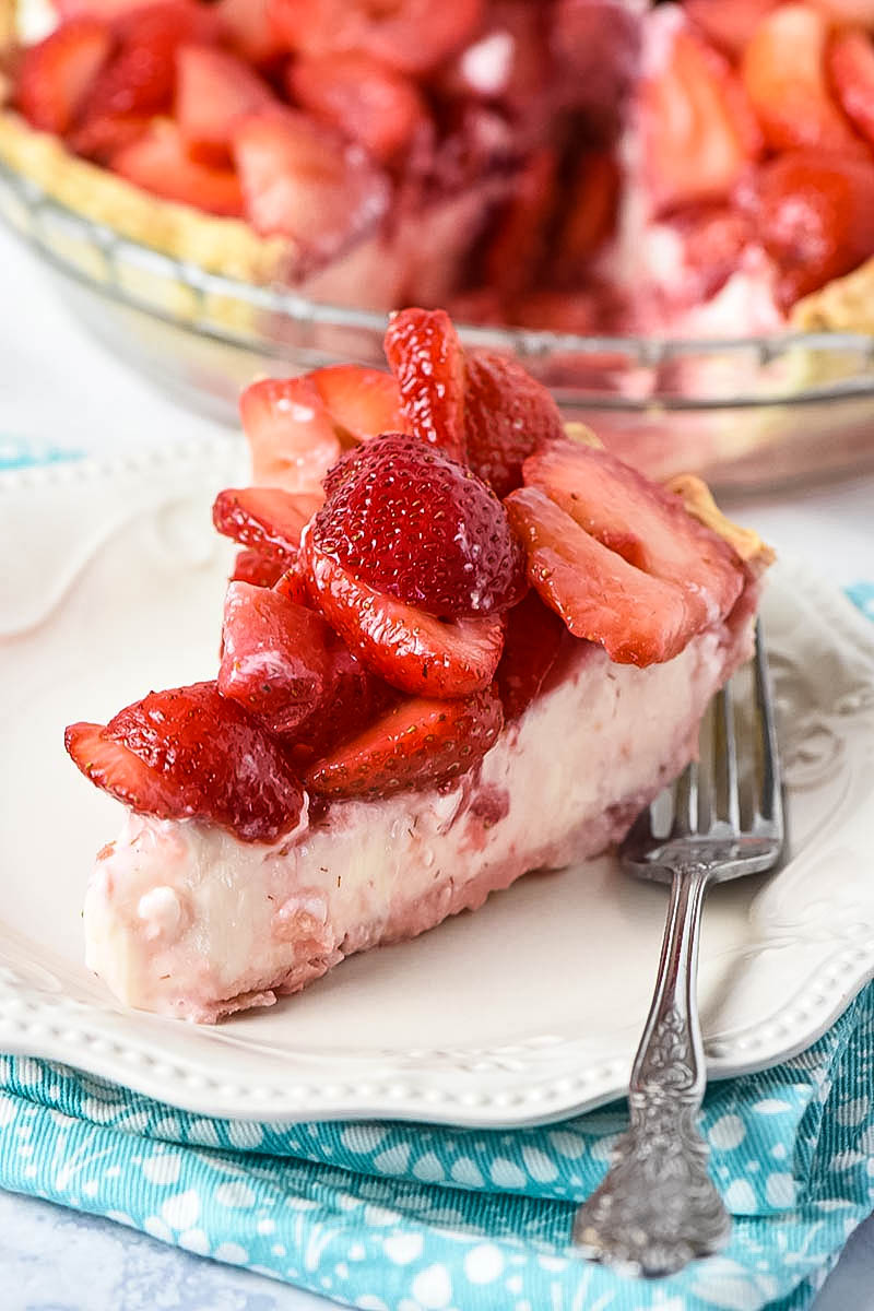 slice of strawberry cream cheese pie on white plate with fork