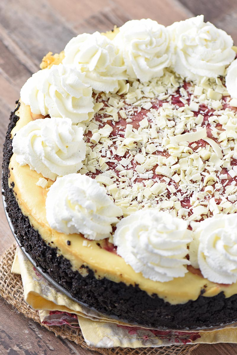 white chocolate raspberry cheesecake with whipped cream swirls on wood countertop