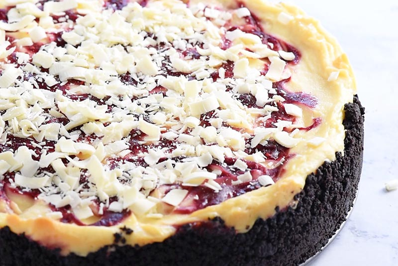 shredded white chocolate on top of raspberry swirl cheesecake