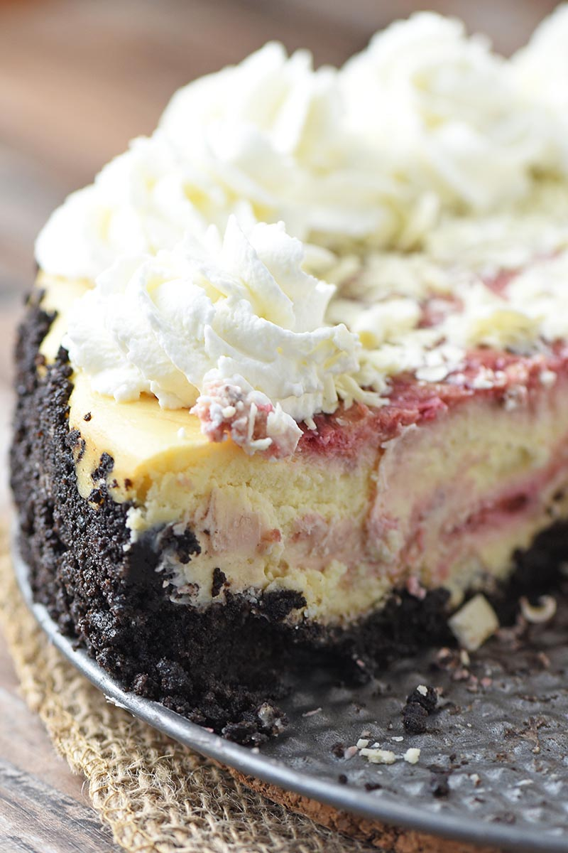 sliced white chocolate raspberry swirl cheesecake with chocolate cookie crust on springform pan bottom