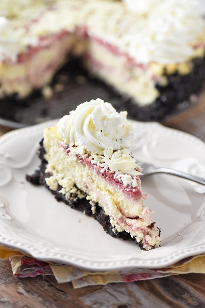 slice of white chocolate raspberry cheesecake on white plate with fork