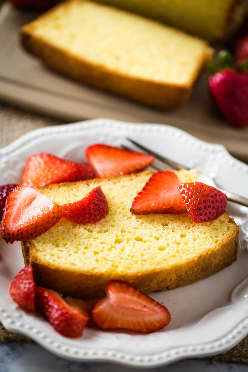 slice of pound cake with strawberries on white plate with fork