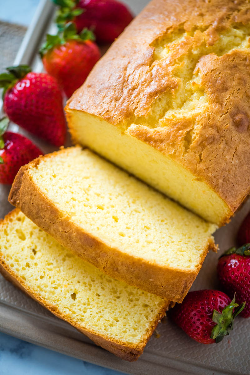 sliced cream cheese pound cake on tan cutting board with fresh strawberries