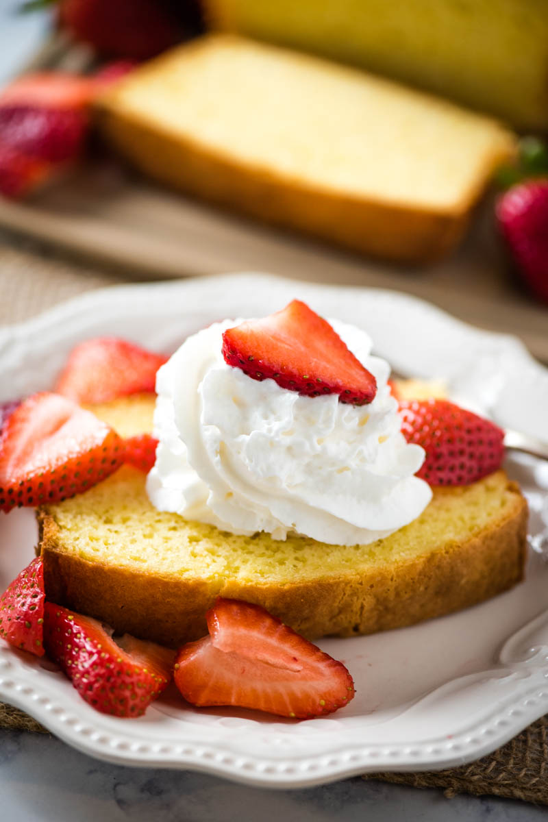 moist pound cake topped with whipped cream and fresh strawberries on white plate