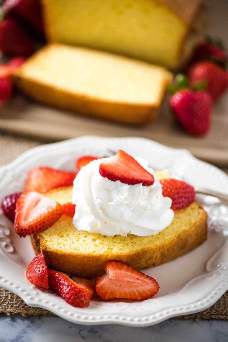 sliced pound cake with whipped cream and strawberries on white plate