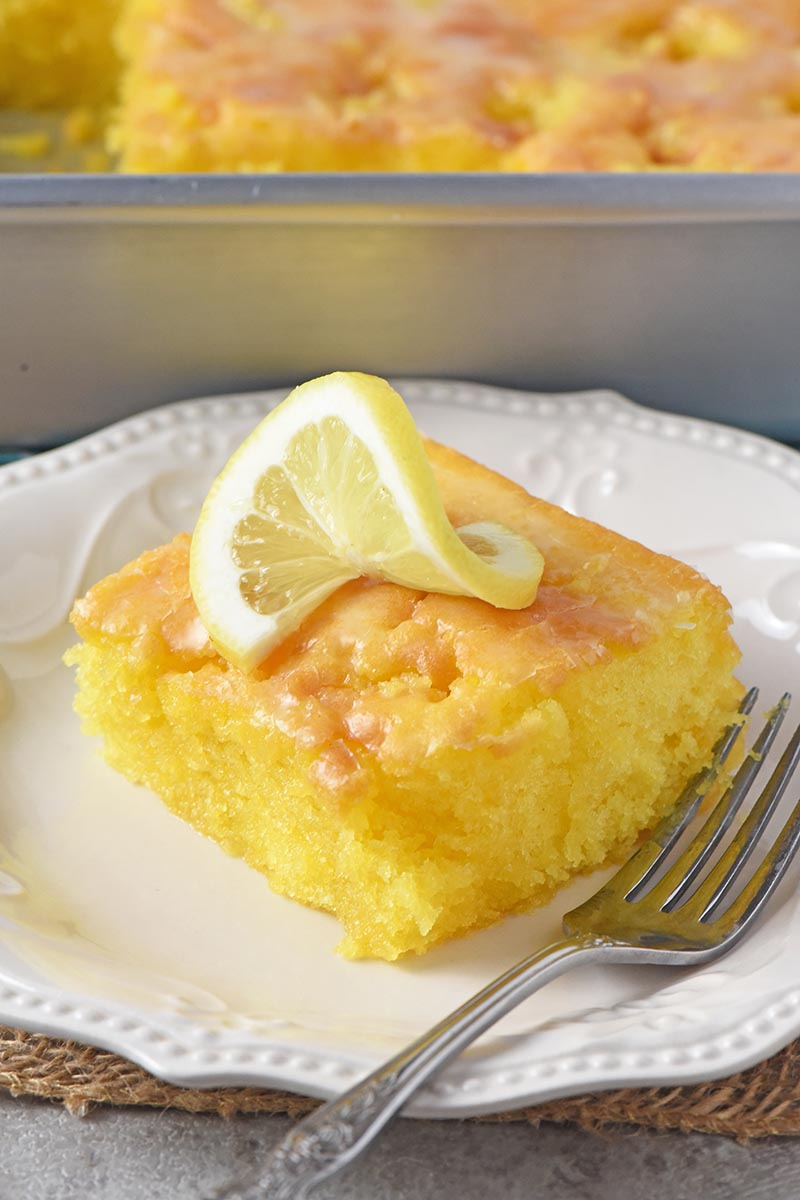 slice of lemon sheet cake on white plate with fork and slice of lemon