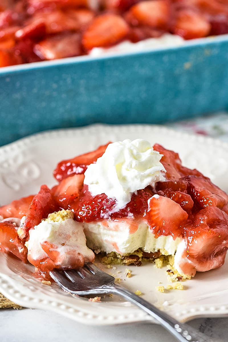 slice of no bake strawberry dessert with whipped cream and bite on white plate with fork