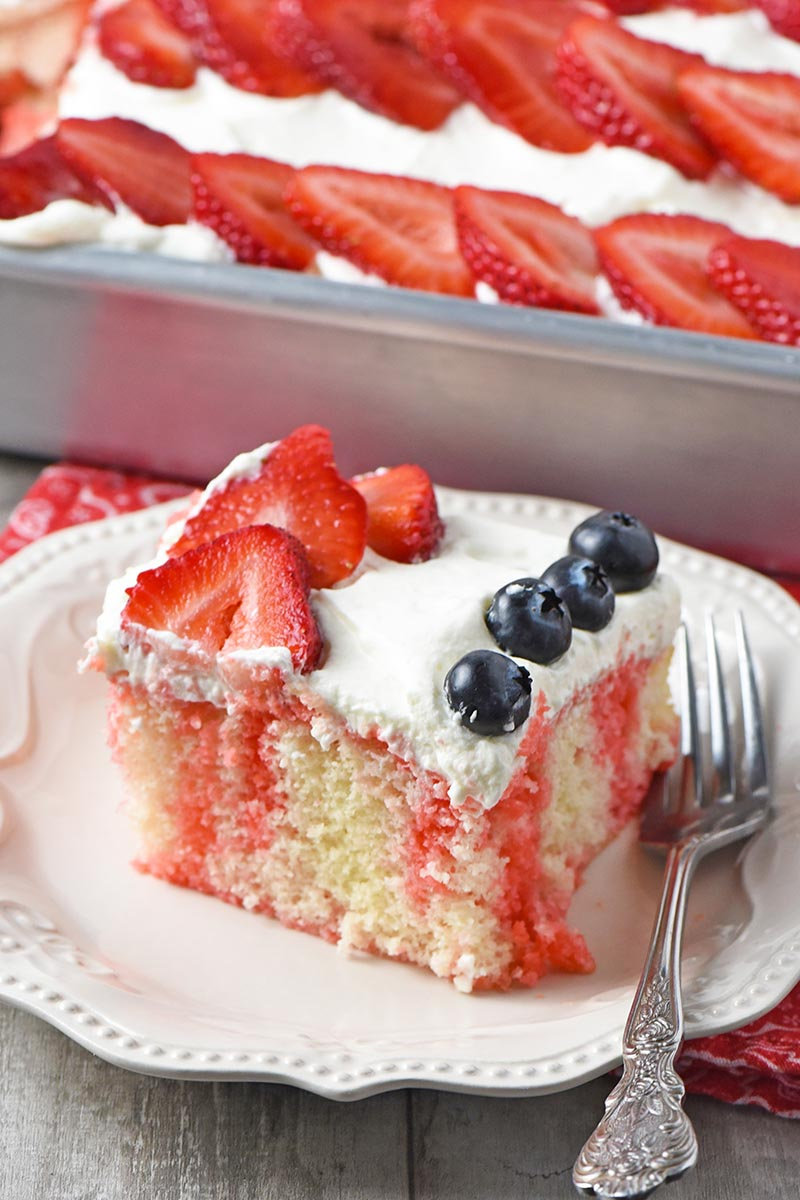 sliced strawberry poke cake with fresh berries on white plate with fork