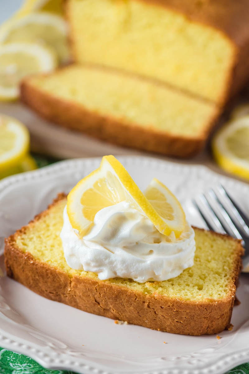 slice of lemon pound cake on white plate with whipped cream and slice of fresh lemon on top of the cake
