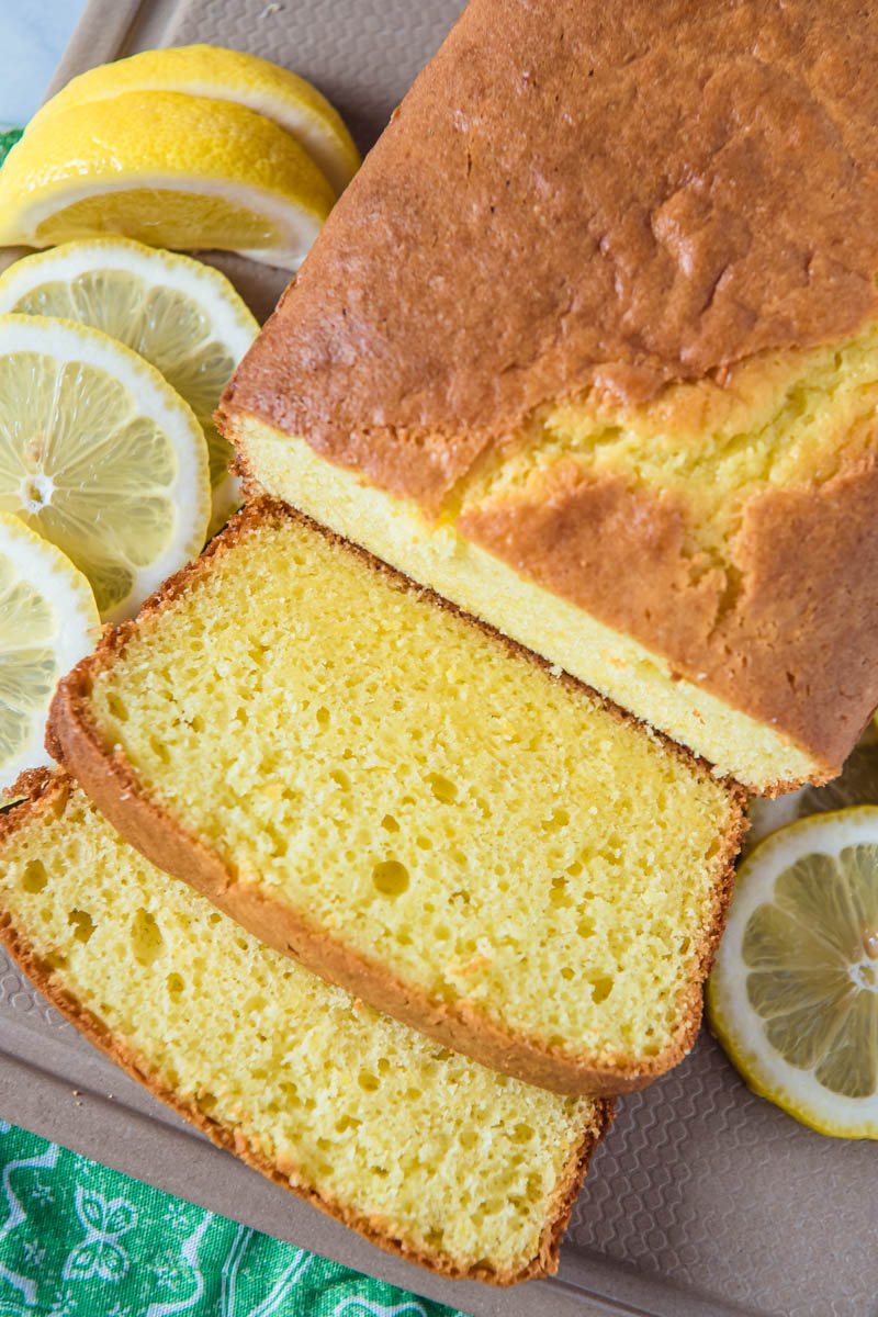 sliced loaf of lemon cream cheese pound cake on tan cutting board with fresh lemon slices and lemon wedges