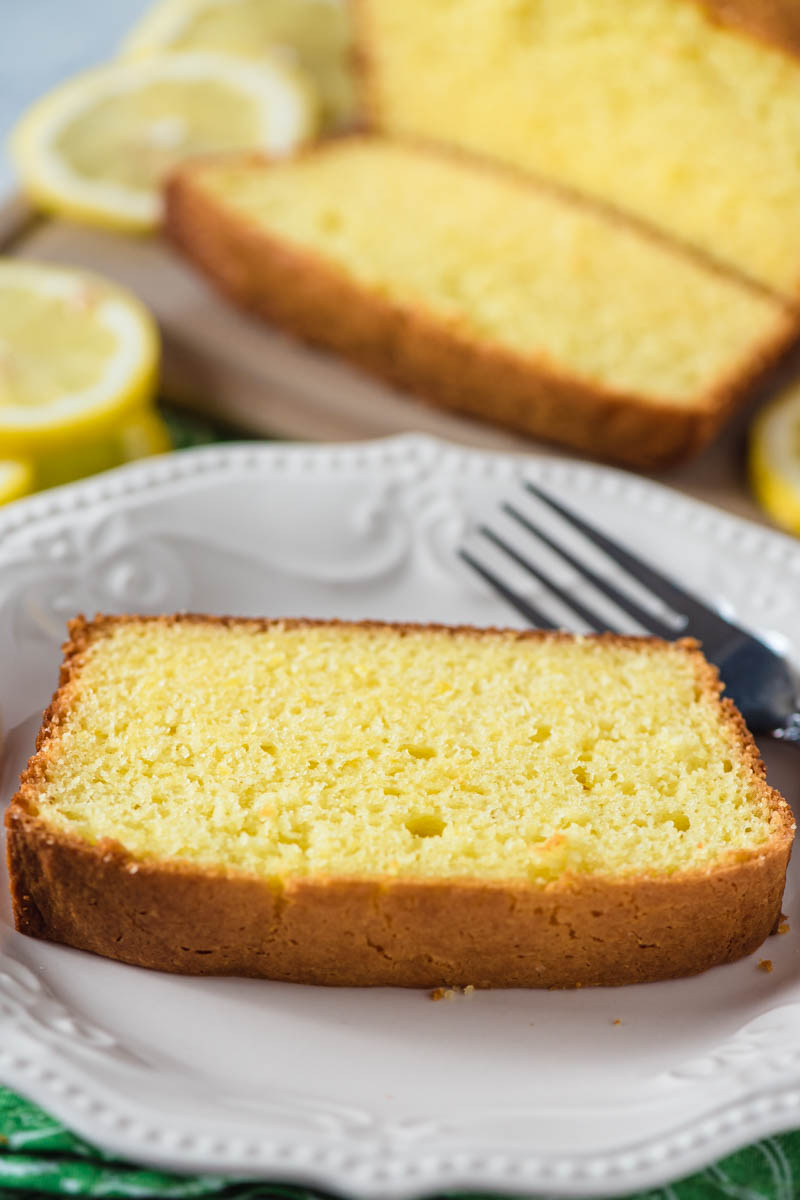 plain slice of moist lemon pound cake on white plate with fork