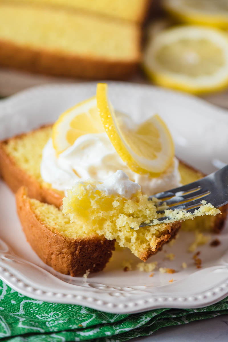 bite of moist lemon pound cake on fork with slice of cake on white plate in background