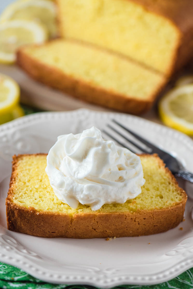 sliced lemon pound cake with dollop of whipped cream on white plate with fork