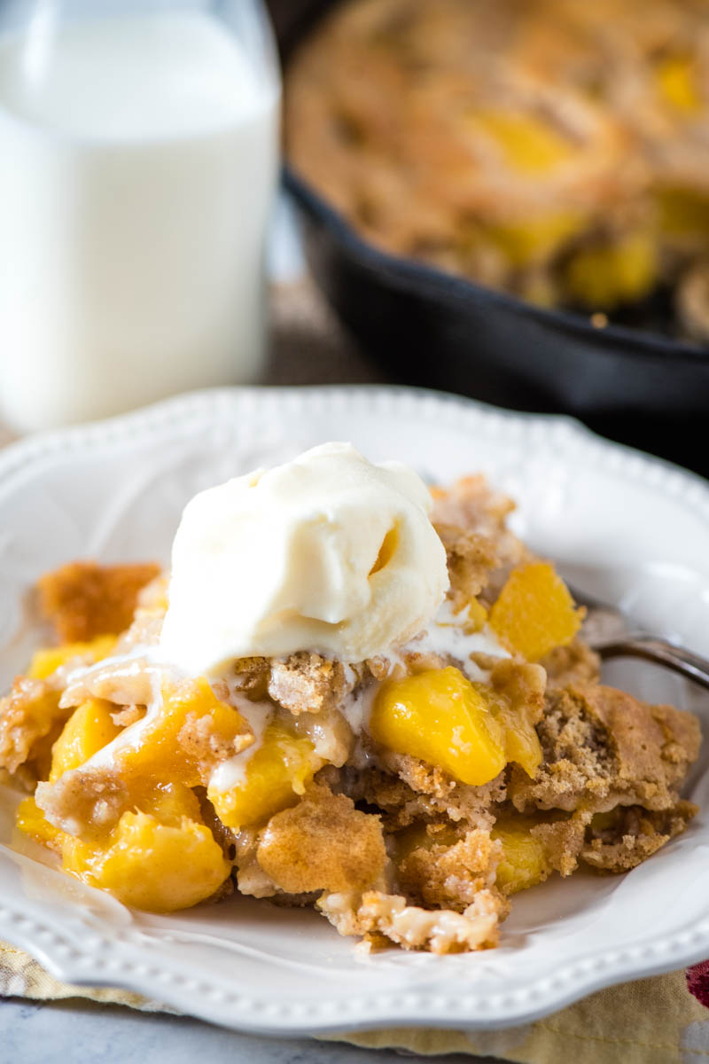 easy peach cobbler with Bisquick served on white plate with vanilla ice cream