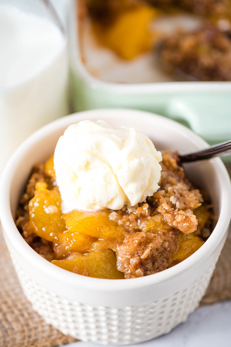 easy peach crisp with scoop of vanilla ice cream on top in white ramekin dish