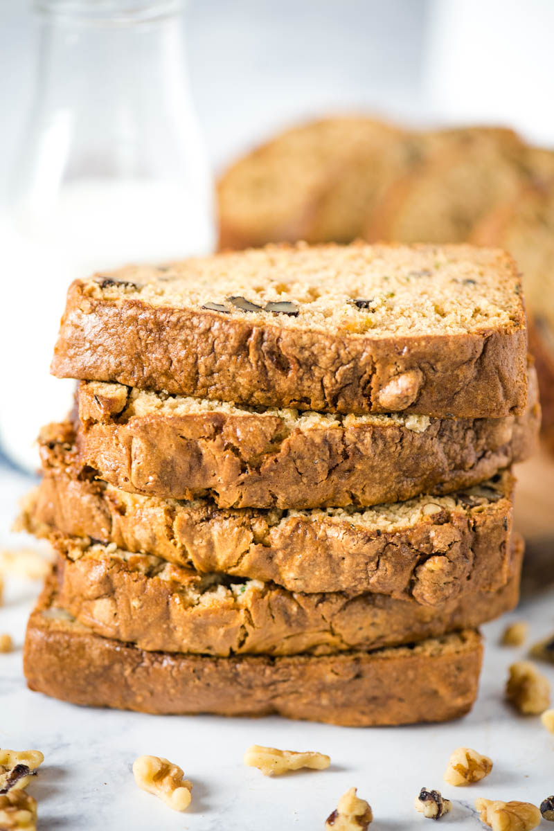 stacked slices of gluten-free zucchini bread with walnuts and glass of milk on white marble countertop