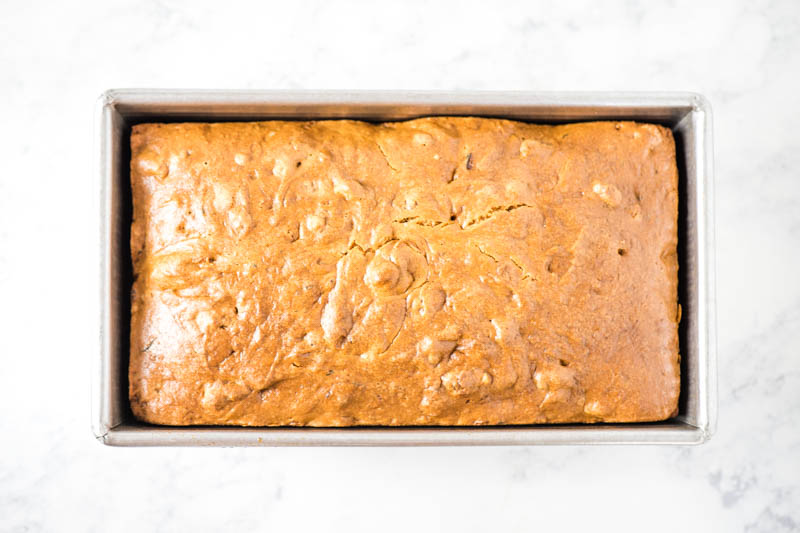 baked zucchini bread in metal loaf pan on white marble countertop