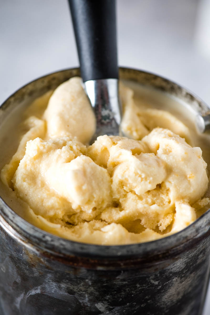 scooping peach ice cream out of metal ice cream maker canister with ice cream scoop