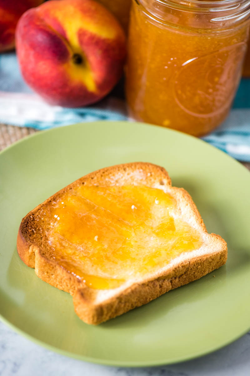 peach freezer jam spread on toast on green plate