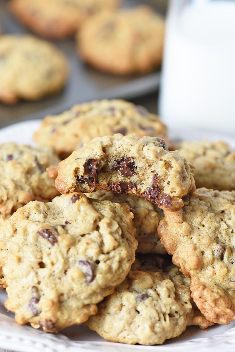 oatmeal cookies with chocolate chips piled on white plate