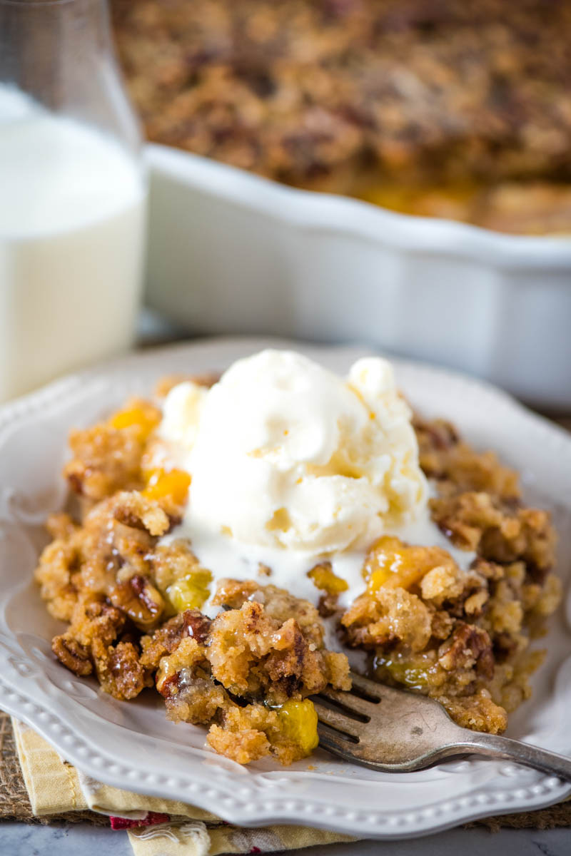 bite of gluten-free peach dump cake on fork with white plate