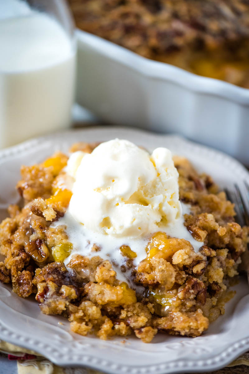 peach dump cake with scoop of vanilla ice cream on white plate with fork and glass of milk
