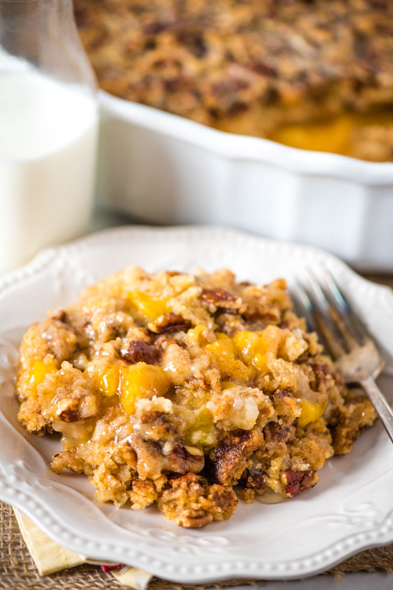 peach pie filling dump cake on white plate with fork and glass bottle of milk