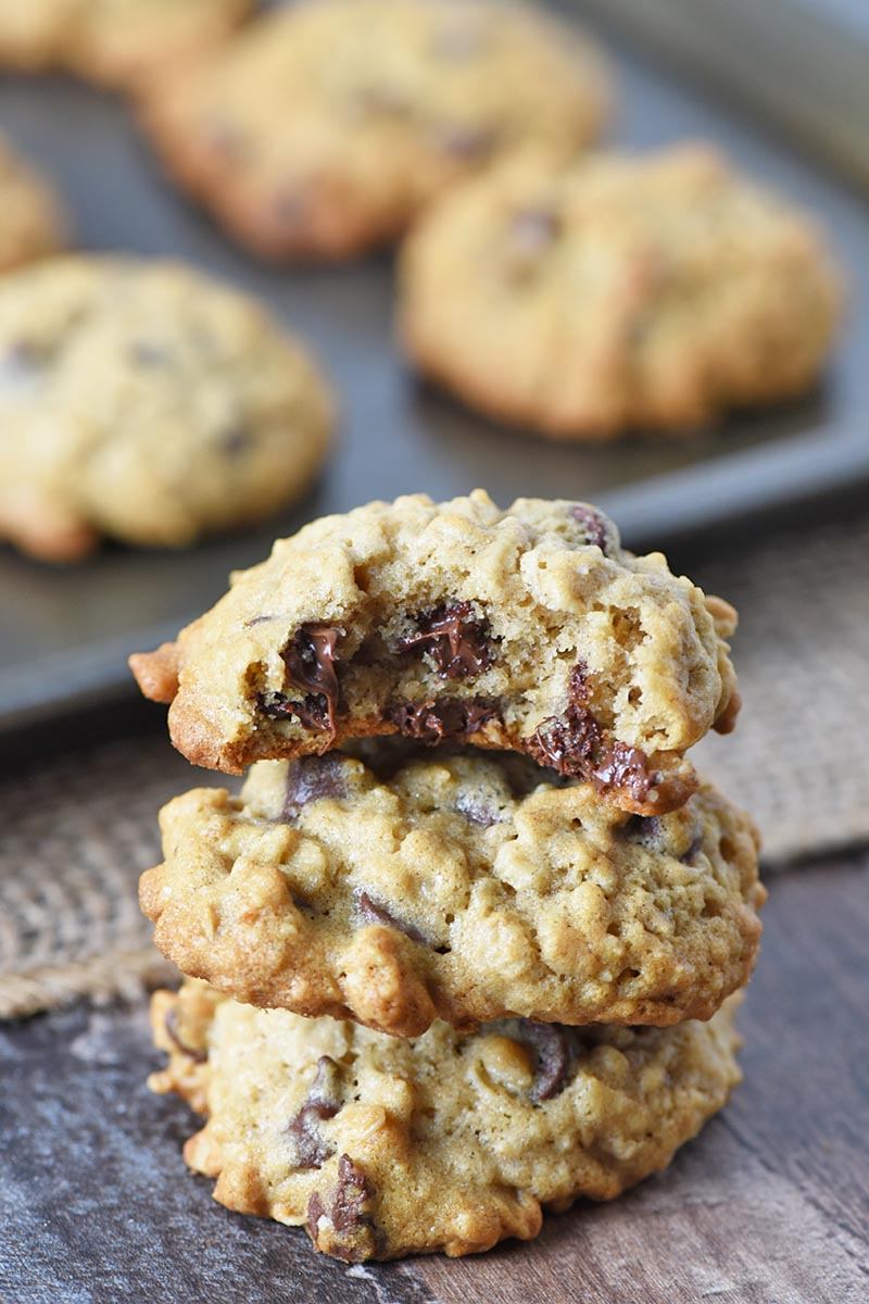 soft oatmeal chocolate chip cookies stacked on wooden countertop