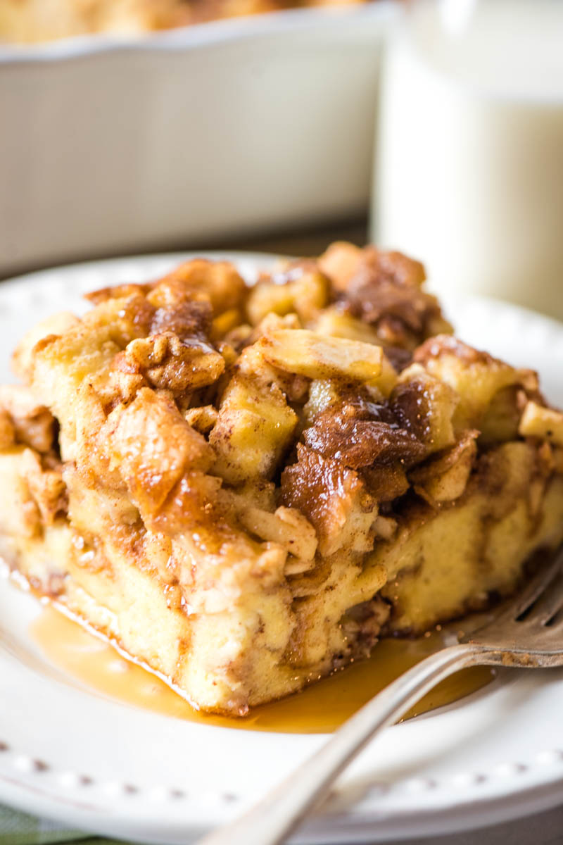 apple cinnamon breakfast casserole served with maple syrup on white plate with fork
