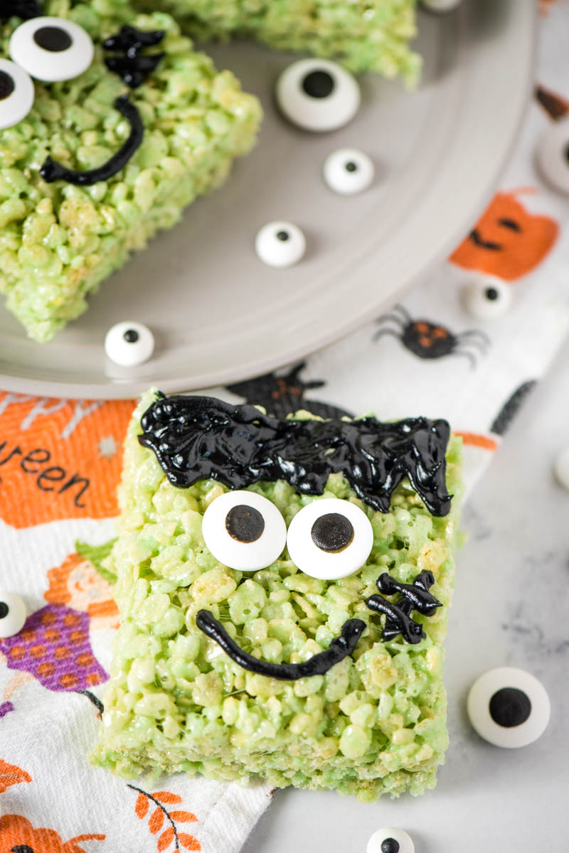 Frankenstein marshmallow treats with candy eyes on white marble countertop with Halloween dish towel