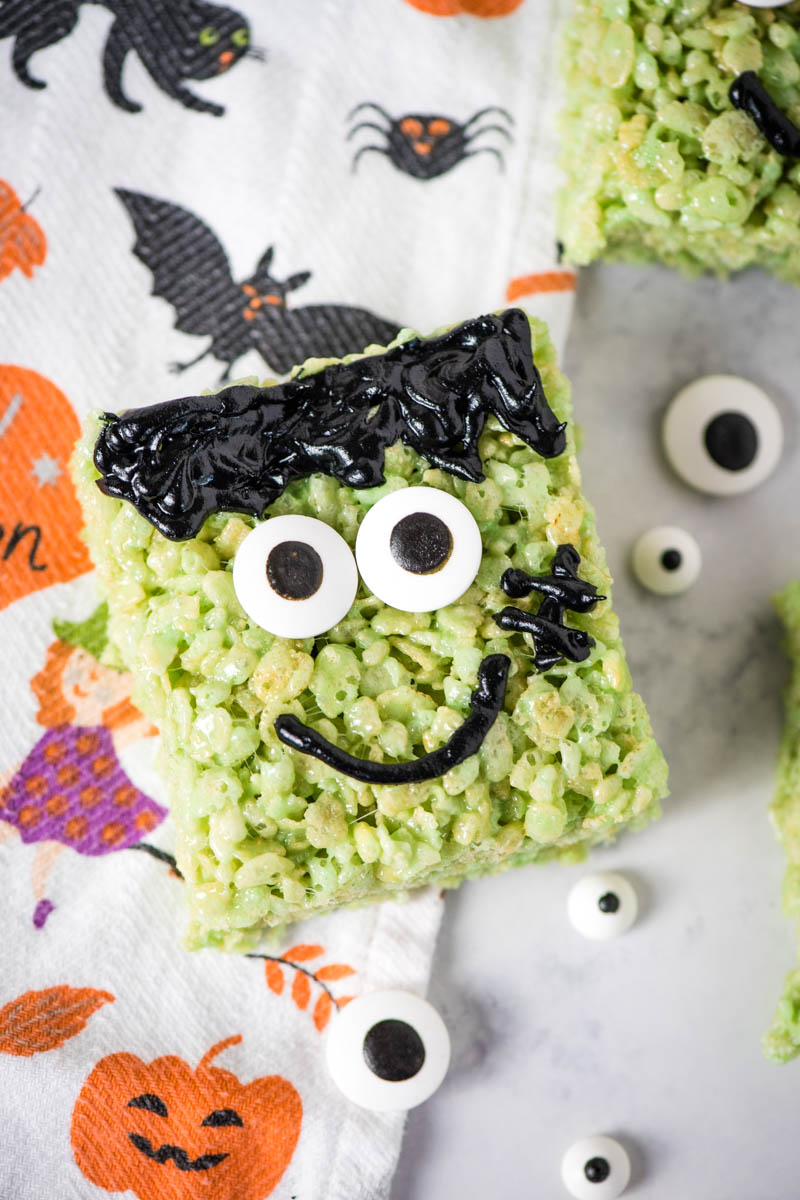 Frankenstein Rice Krispie treats on white marble countertop with candy eyes and Halloween dish towel