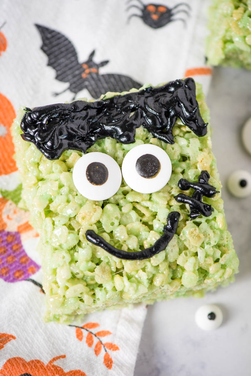 green Halloween cereal treats decorated like Frankenstein on white marble countertop with Halloween dish towel