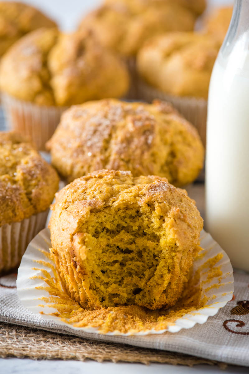moist and fluffy inside of gluten-free pumpkin muffins on white cupcake liner with glass of milk