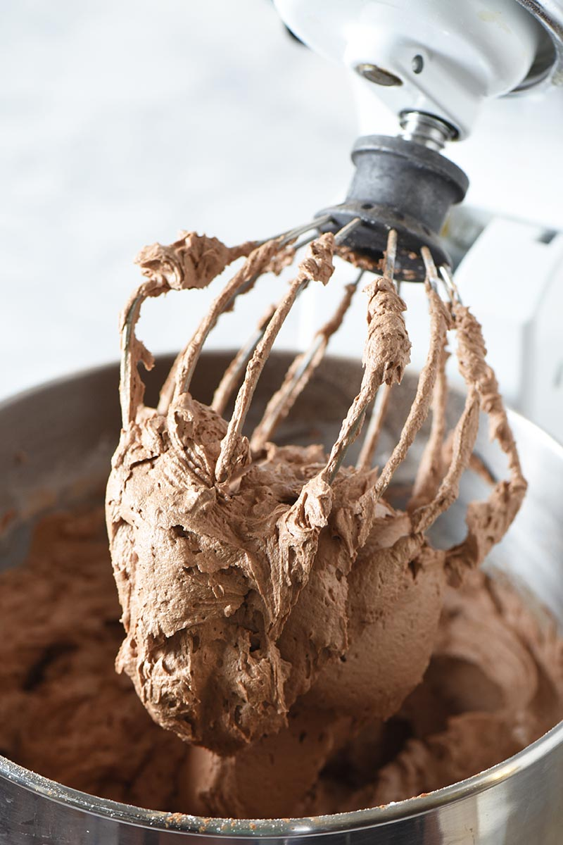 mixing up milk chocolate buttercream frosting with KitchenAid mixing whisk