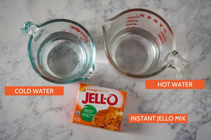 box Jello ingredients, including orange Jello gelatin mix and hot water and cold water in glass measuring cups on white marble countertop