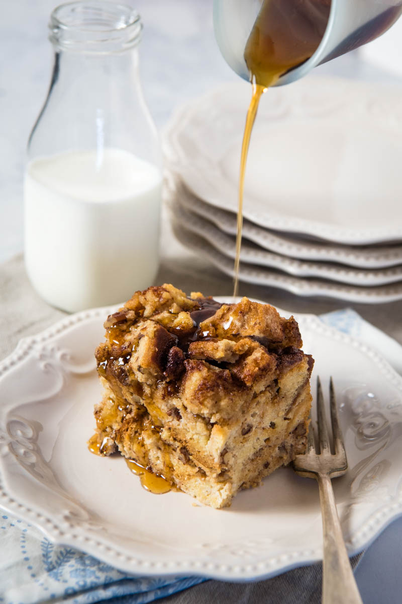pouring maple syrup over slice of gluten-free French toast casserole on white plate with fork, glass of milk in background