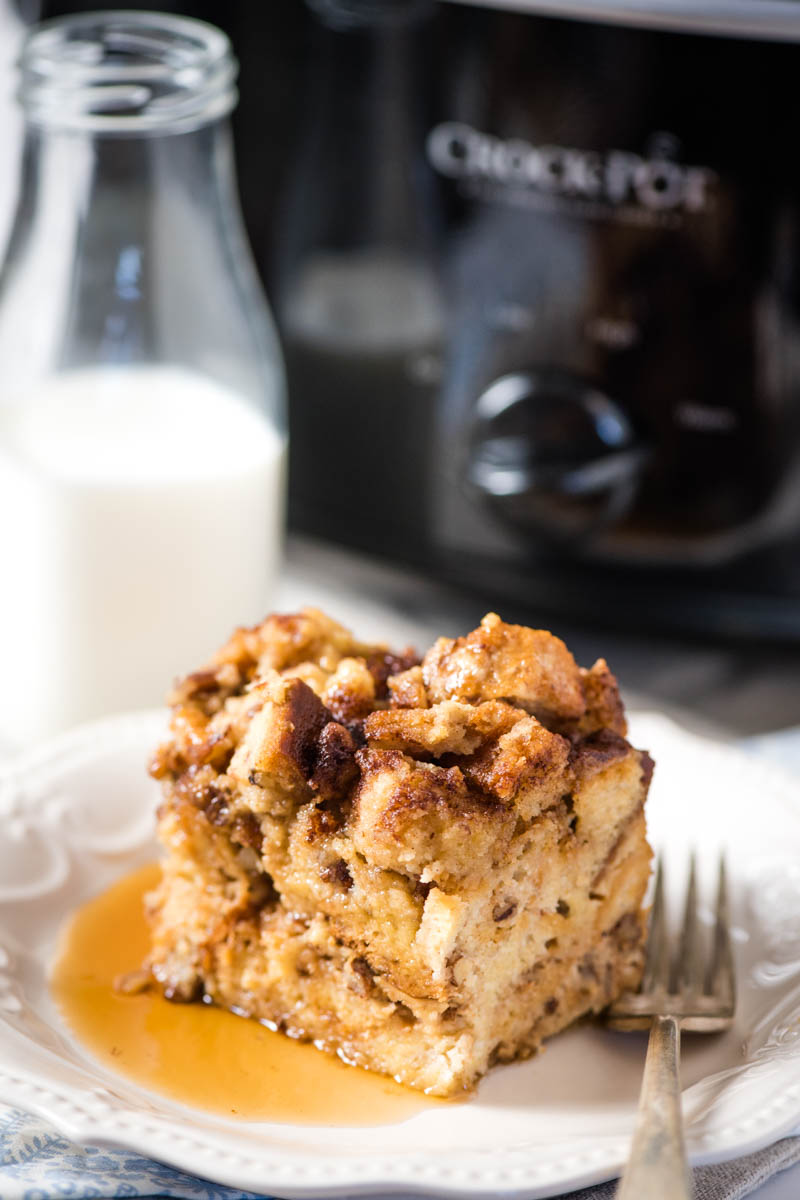 slice of slow cooker French toast breakfast casserole on white plate with fork, with black Crock Pot slow cooker in background