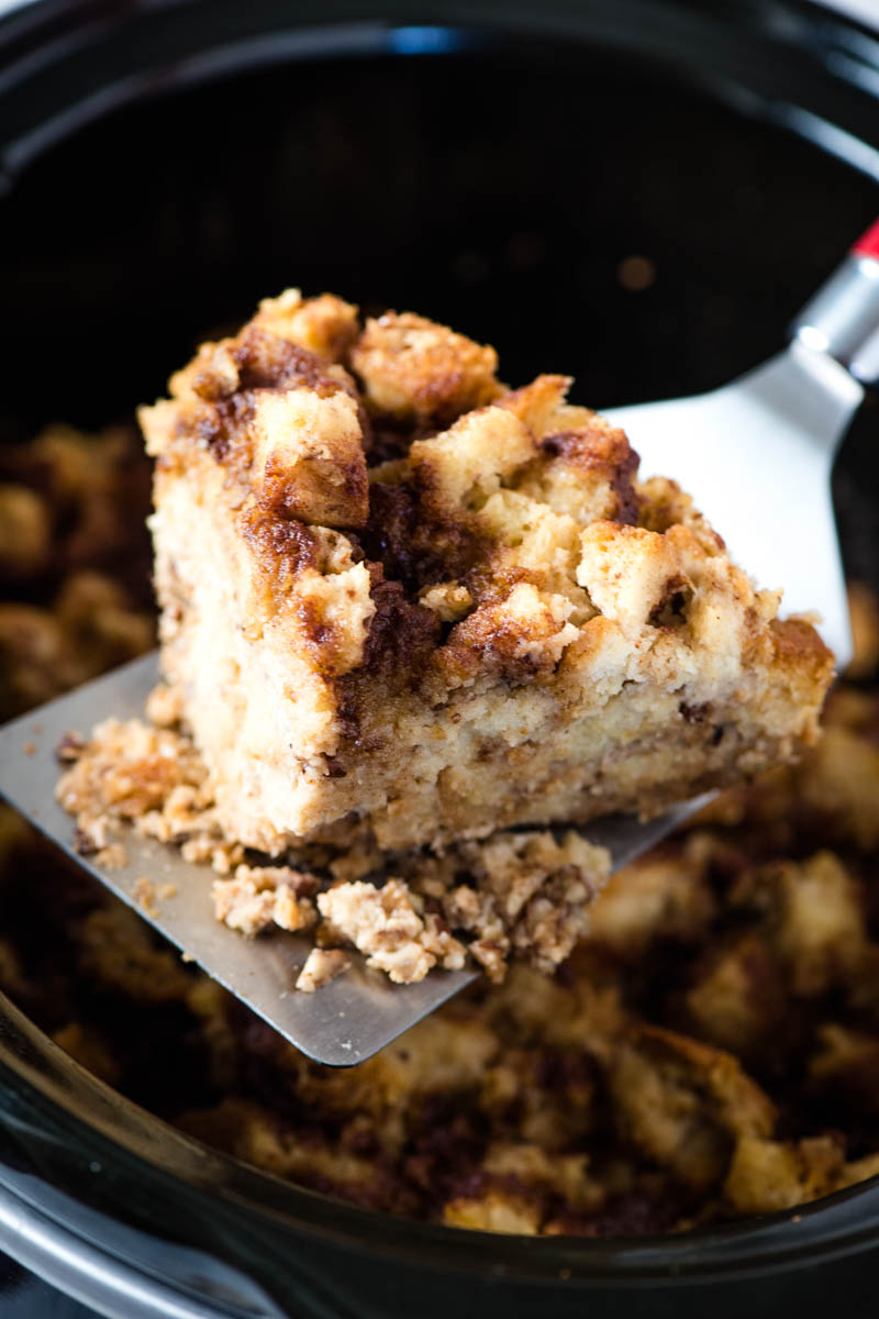 slicing and scooping slow cooker French toast out of Crock Pot with wide flipper spatula
