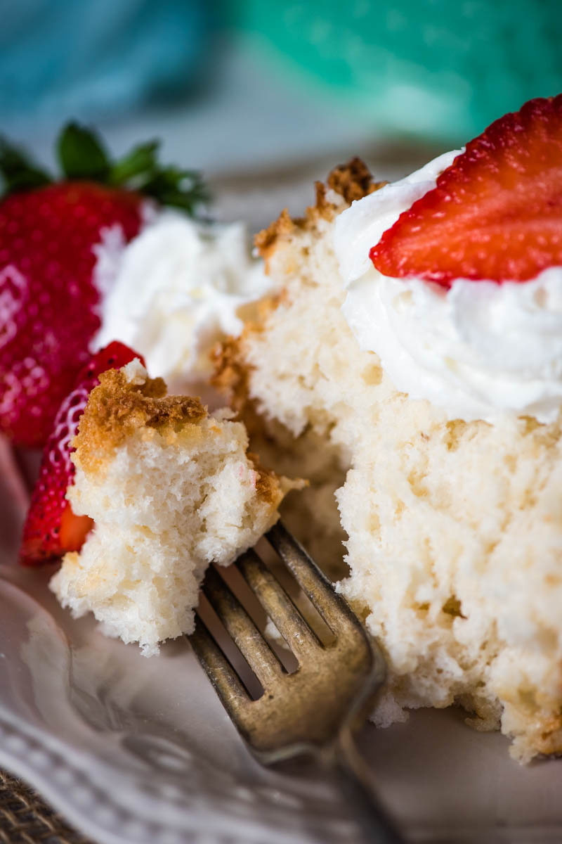 bite of angel food cake with strawberries on white plate with fork
