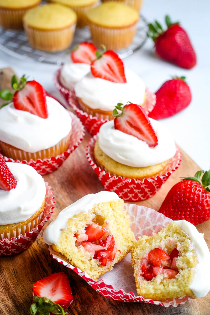 vanilla cupcakes filled with fresh strawberries and topped with whipped cream frosting and fresh strawberry slices, in red cupcake liners, on wooden cutting board