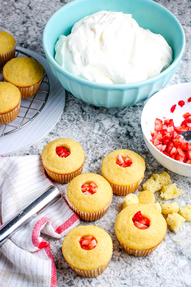 strawberry filled vanilla cupcakes with red and white kitchen towel and apple corer on granite countertop with light blue bowl of whipped cream frosting