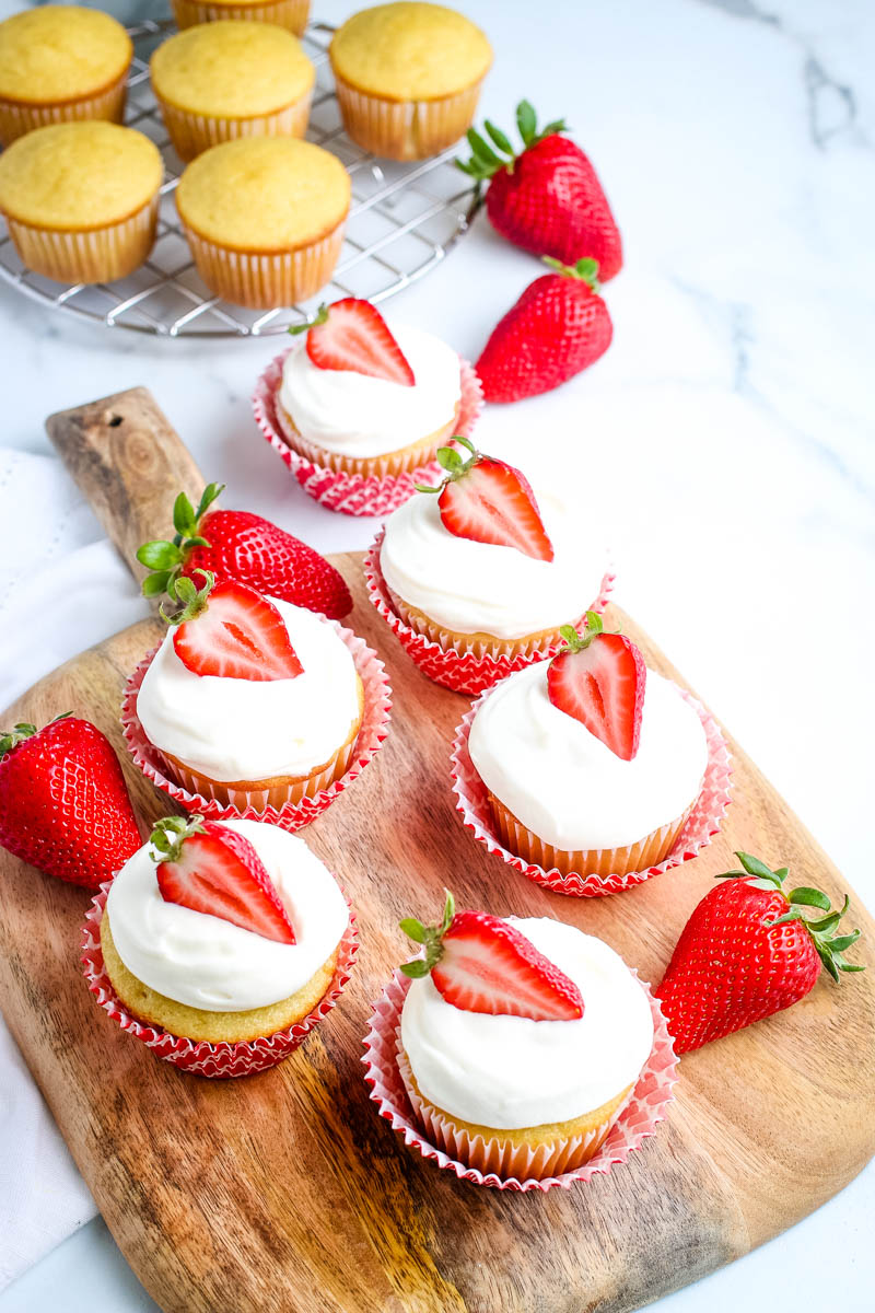 strawberry and whipped cream topped cupcakes sitting in red cupcake liners on wooden cutting board on white marble countertop