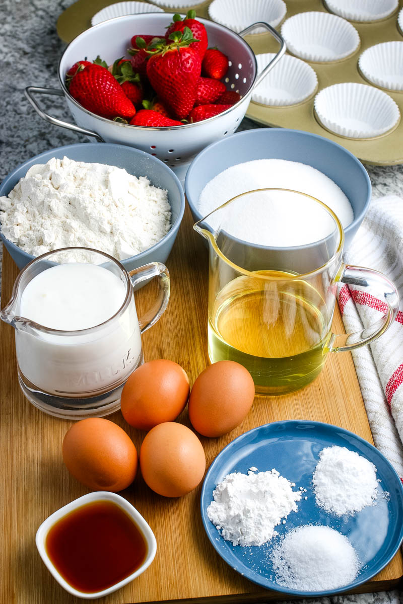 ingredients for shortcake cupcakes, including eggs, vanilla extract, flour, sugar, canola oil, and strawberries in bowls and measuring cups on wooden cutting board